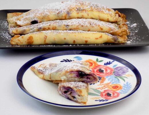 Naleśniki nadziewane białym serem i jagodami, zapiekane na patelni, podawane z cukrem pudrem - Przepis na naleśniki