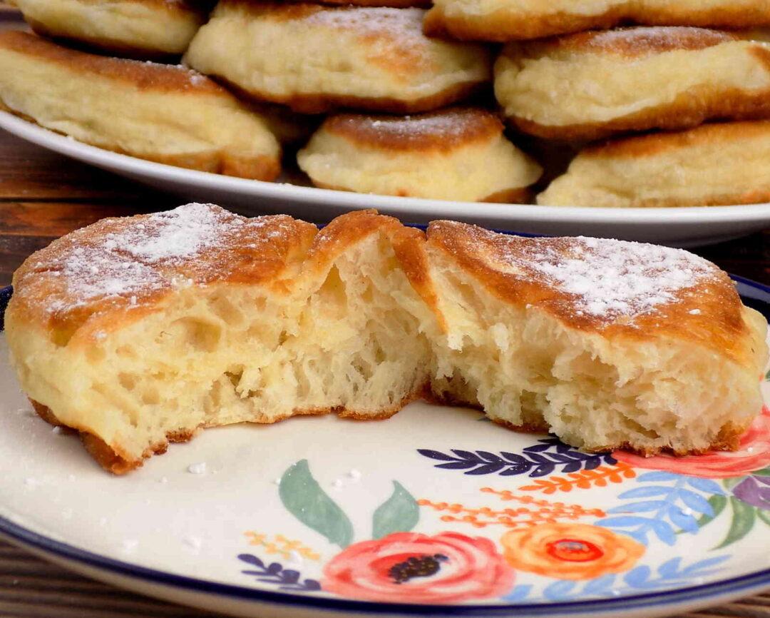 talerz z racuchami drożdżowymi posypanymi cukrem pudrem - racuchy drożdżowe